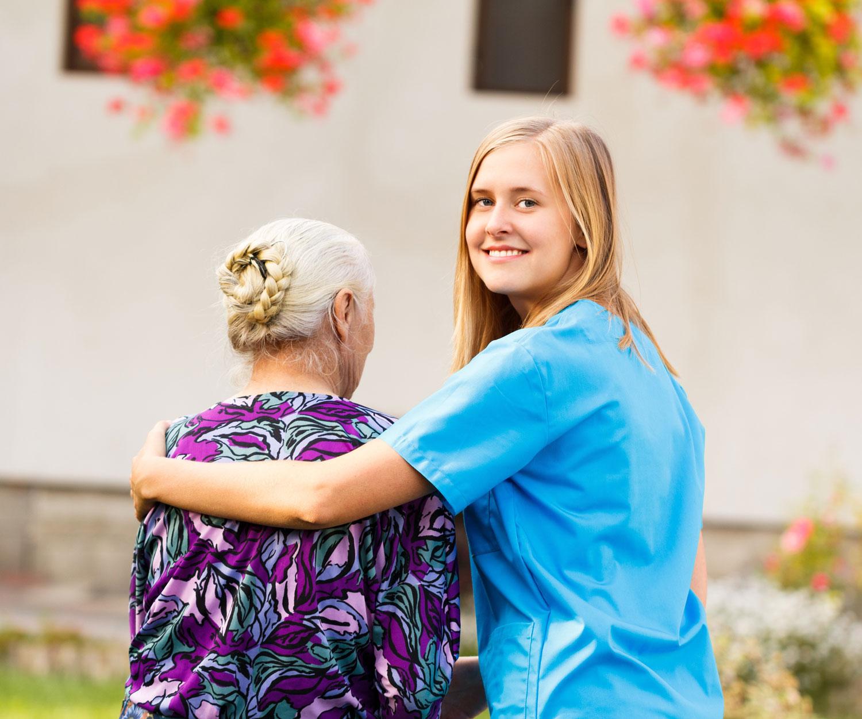 Vårdare inom hemtjänst håller armen om kvinnlig brukare med ansiktet vänt från kameran.
