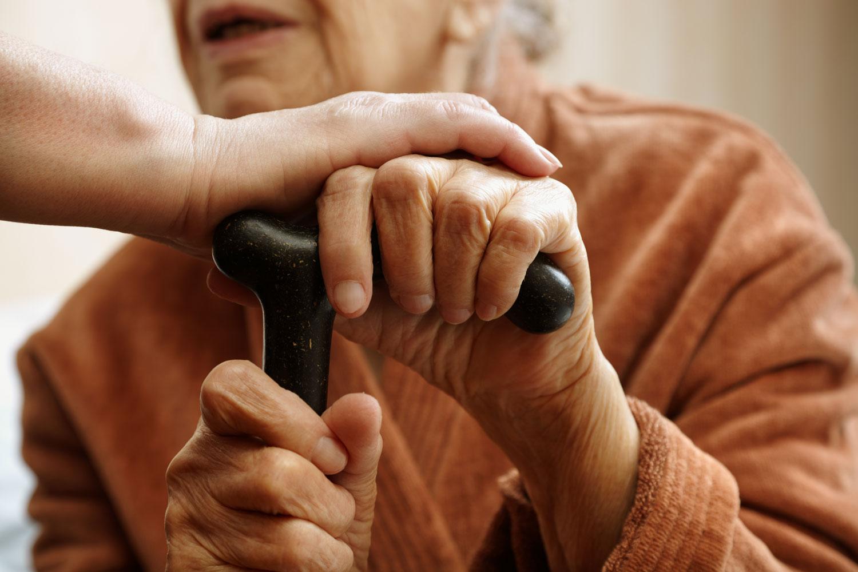 En gammal kvinna håller sina händer på en käpp. Yngre person håller en hand över kvinnans ena hand.
