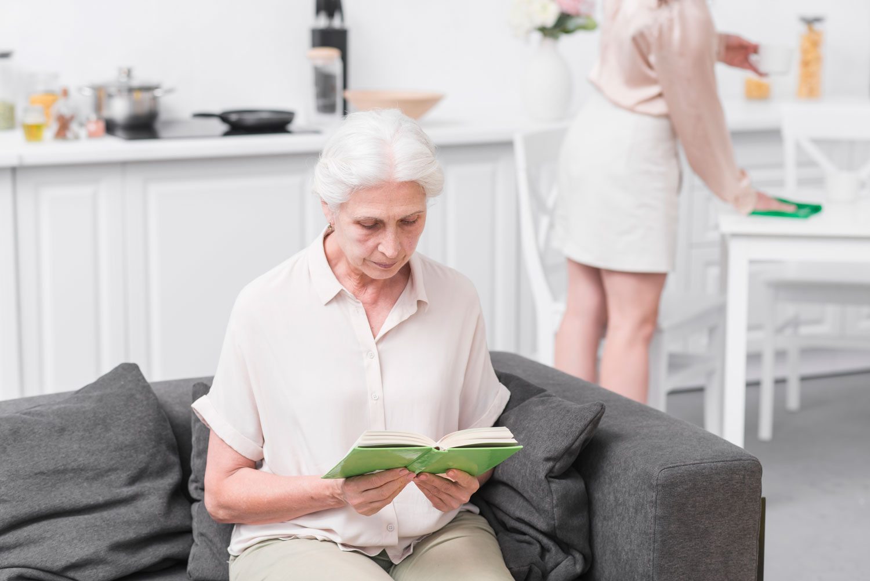 Äldre kvinna sitter i soffan och läser medan yngre kvinna städar i bakgruden