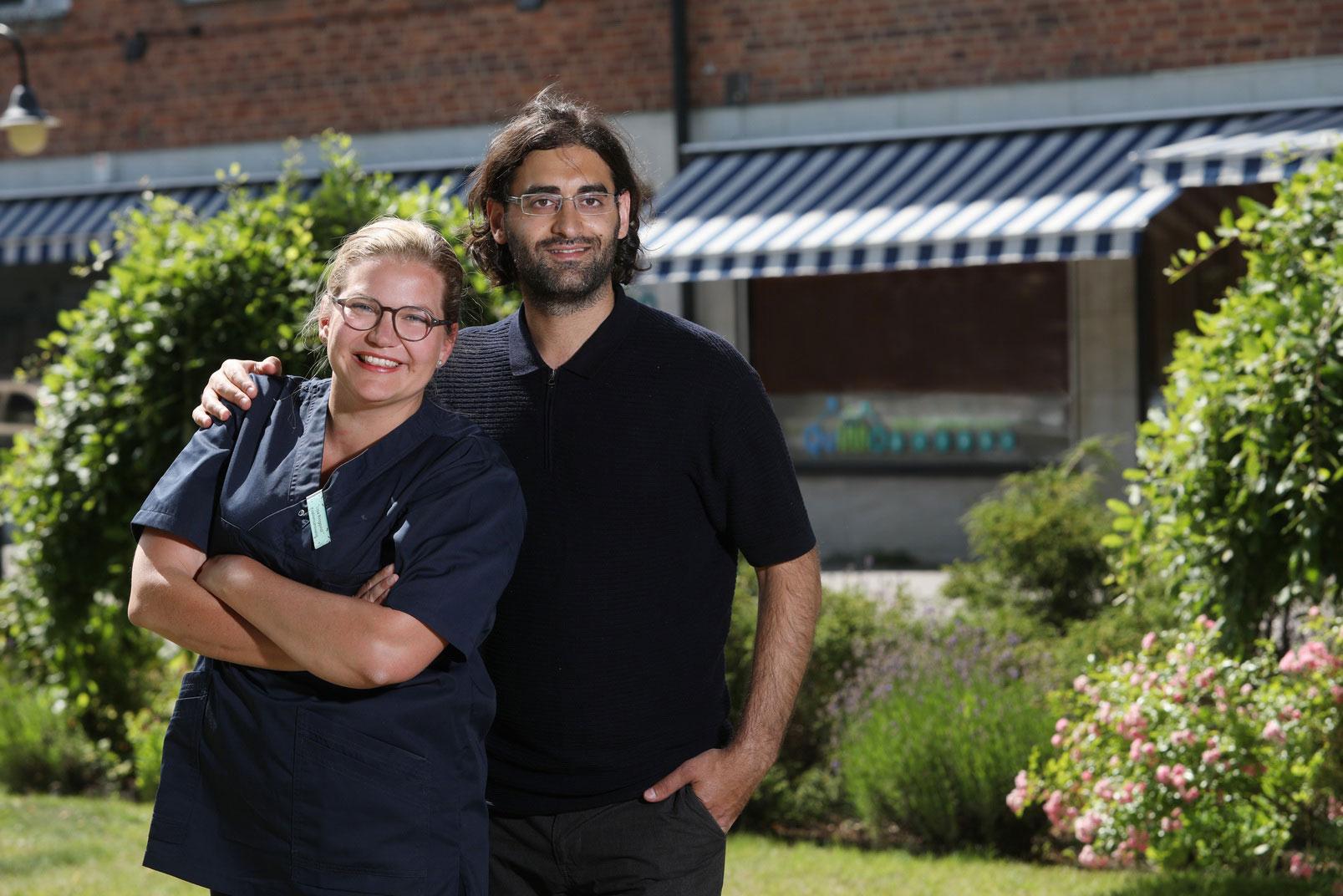 En kvinna och en man står framför kontorsbyggnad.