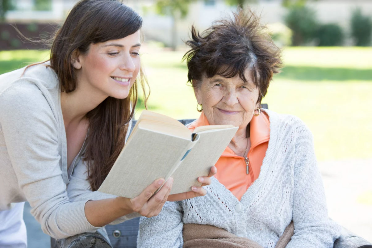 Ung kvinna med mörkt hår läser högt ur bok för äldre kvinna.