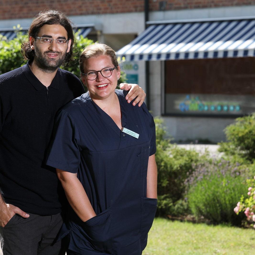 En man och en kvinna står framför en lägenhetsbyggnad. Mannan håller en arm runt kvinnan som har på sig omvårdnadskläder.