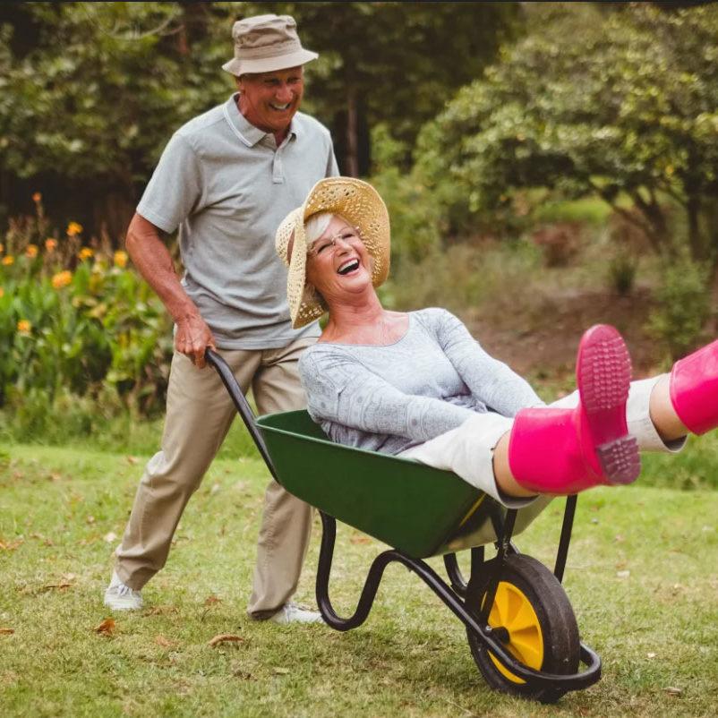 Äldreman i fiskehatt kör äldre kvinna med rosa gummistövlar i skottkärra